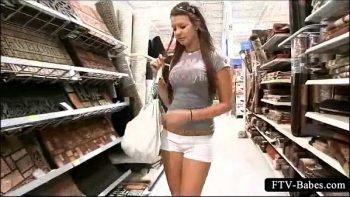 امرأة شابة ذات مؤخرة مثيرة موجودة في متجر وتلعب بأصابعها على كسها